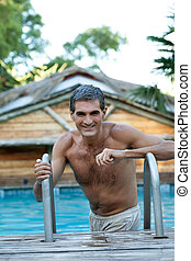 Smiling Middle Aged Man Standing in Pool - Portrait of...