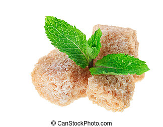 Three brown lump cane sugar cubes with peppermint leaves,...