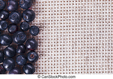 Many bilberry fruits, on gray linen table cloth with copy...