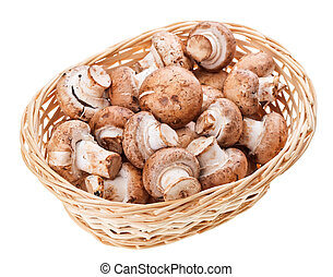 Brown champignon mushrooms in wicker wooden basket, isolated...