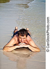 Man in bathingsuit is lying at the beach and enjoying the...