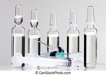 Syringes and vials 2 - Syringes and vials placed on a white...