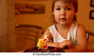 Birthday cake against a background of a little girl