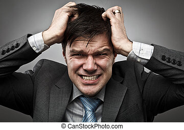 Businessman pulling his hair - Frustrated young businessman...