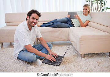 Woman using a tablet computer while her boyfriend is using a...