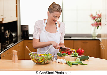 Woman slicing vegetables in her kitchen