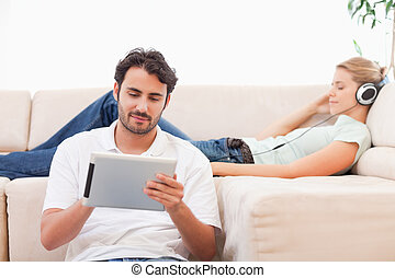 Man using a tablet computer while his girlfriend is...