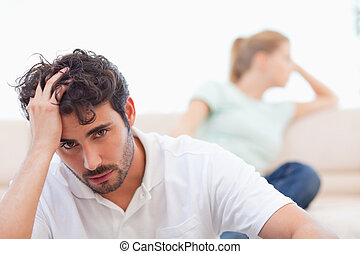 Sad couple mad at each other in their living room