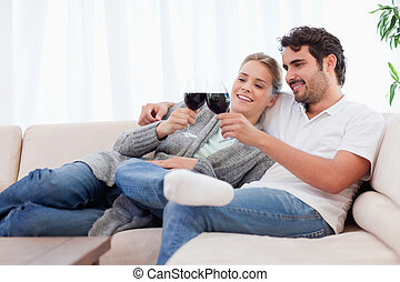 Couple having a glass of red wine in their living room
