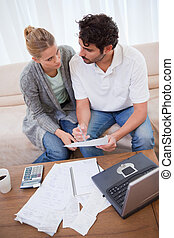 Portrait of a young couple doing their accounting with a notebook in their living room
