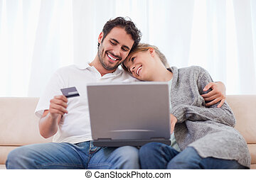 Happy couple shopping online in their living room