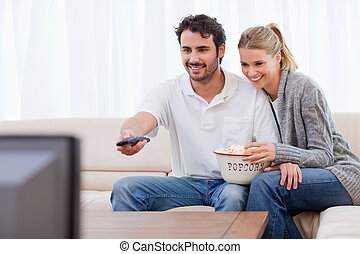 Smiling couple watching TV while eating popcorn in their...