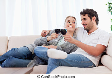 Couple having a glass of wine in their living room