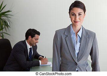 Beautiful businesswoman posing while her colleague is working
