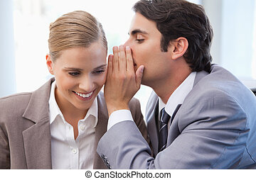 Businessman whispering something to his colleague in a...