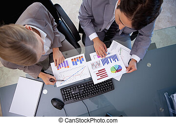 Business team looking at statistics in a meeting room