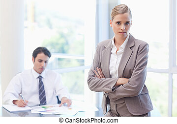 Serious businesswoman posing while her colleague is working...