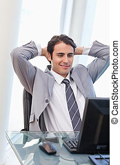 Portrait of a relaxed businessman working with a computer in...