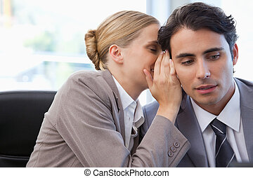 Businesswoman whispering something to her colleague in a...