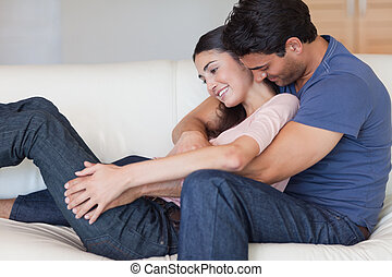Man kissing his girlfriend in the neck in their living room