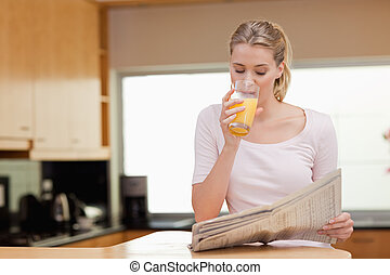 Young woman reading the news while drinking orange juice