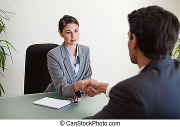 Young manager shaking the hand of a customer