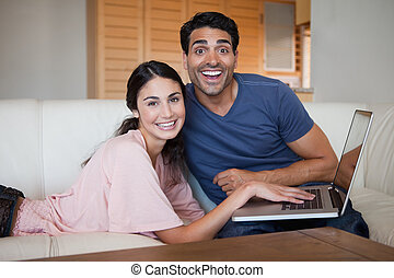 Laughing young couple using a notebook