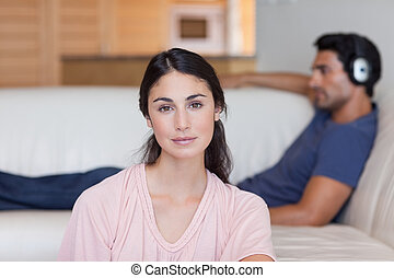 Woman posing while her boyfriend is listening to music