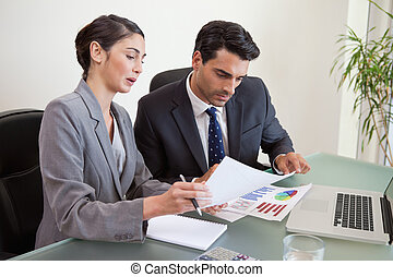 Sales persons working with a notebook in an office