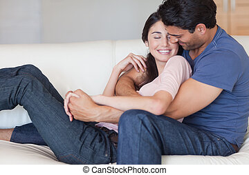 Man kissing his fiance in the neck in their living room
