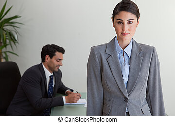 Gorgeous businesswoman posing while her colleague is working...