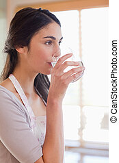 Portrait of a woman drinking water in her kitchen