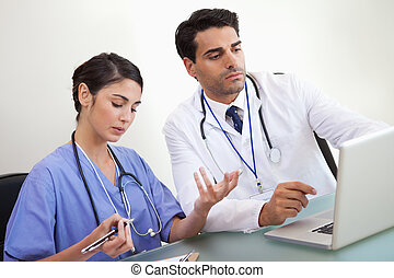 Doctors working with a laptop in an office