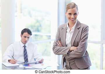 Smiling businesswoman posing while her colleague is working