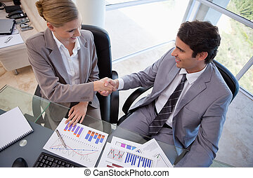 Business people agreeing on a deal in a meeting room