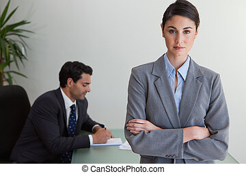 Professional businesswoman posing while her colleague is...