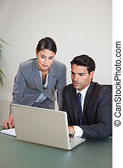 Portrait of sales persons working with a notebook in an...