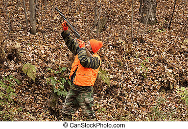 autumn hunter - hunter aiming his weapon in the autumn woods