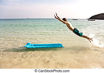 boy with red hair is enjoying jumping on the air mattress at...