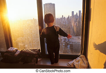 young boy looks fascinated from the skyscraper to the...