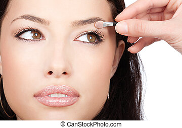 Pretty girl receives eyeshadow from make-up artist, isolated...