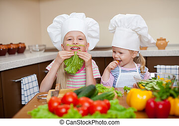 two little girls preparing healthy food and have fun on...