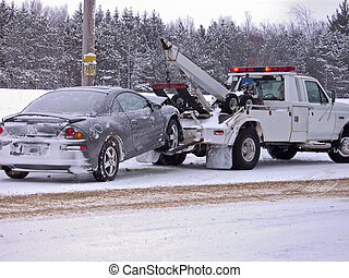 Tow Truck - Wrecked car being towed away by tow truck.