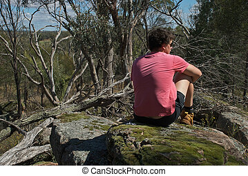 rural - a young man deep in thought sitting