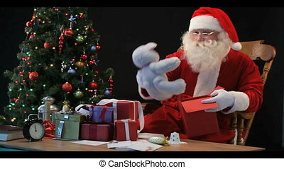 Timelapse of Santa wrapping gifts - Santa Claus wrapping a...
