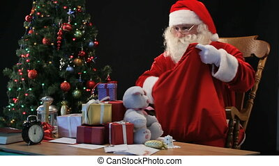 Santa with sack - Santa putting wrapped presents into his...