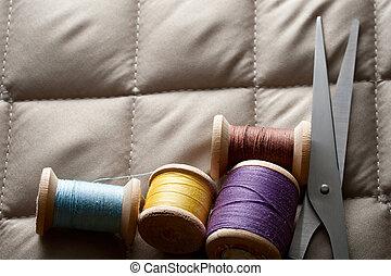 Thread bobbins with scissors on a gray fabric