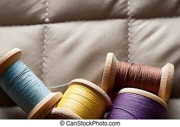 Thread bobbins on a gray fabric