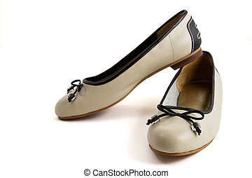 Pair of beige female shoes with black bow over white...