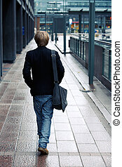 Teenage Boy - Teenage boy walking away from camera in street